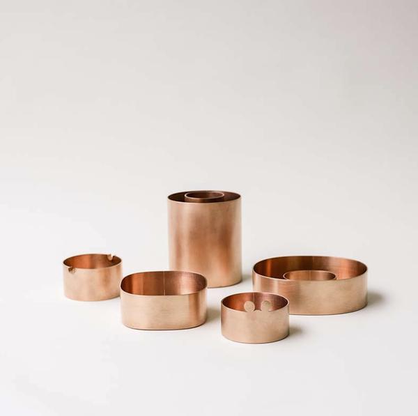 Kim Hyung Sung - Fünf Gefäße aus Kupfer. Zwei davon runde niedrige Aschenbecher, einer mit kleinen runden Ohren als Ablage. Die anderen drei ovale Gefäße, zwei niedrige, ein hohes. Das hohe und ein niedriges als Ring gearbeitet.